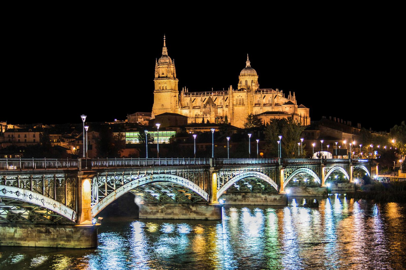 Historic city of Salamanca with river Tormes at night, Spain