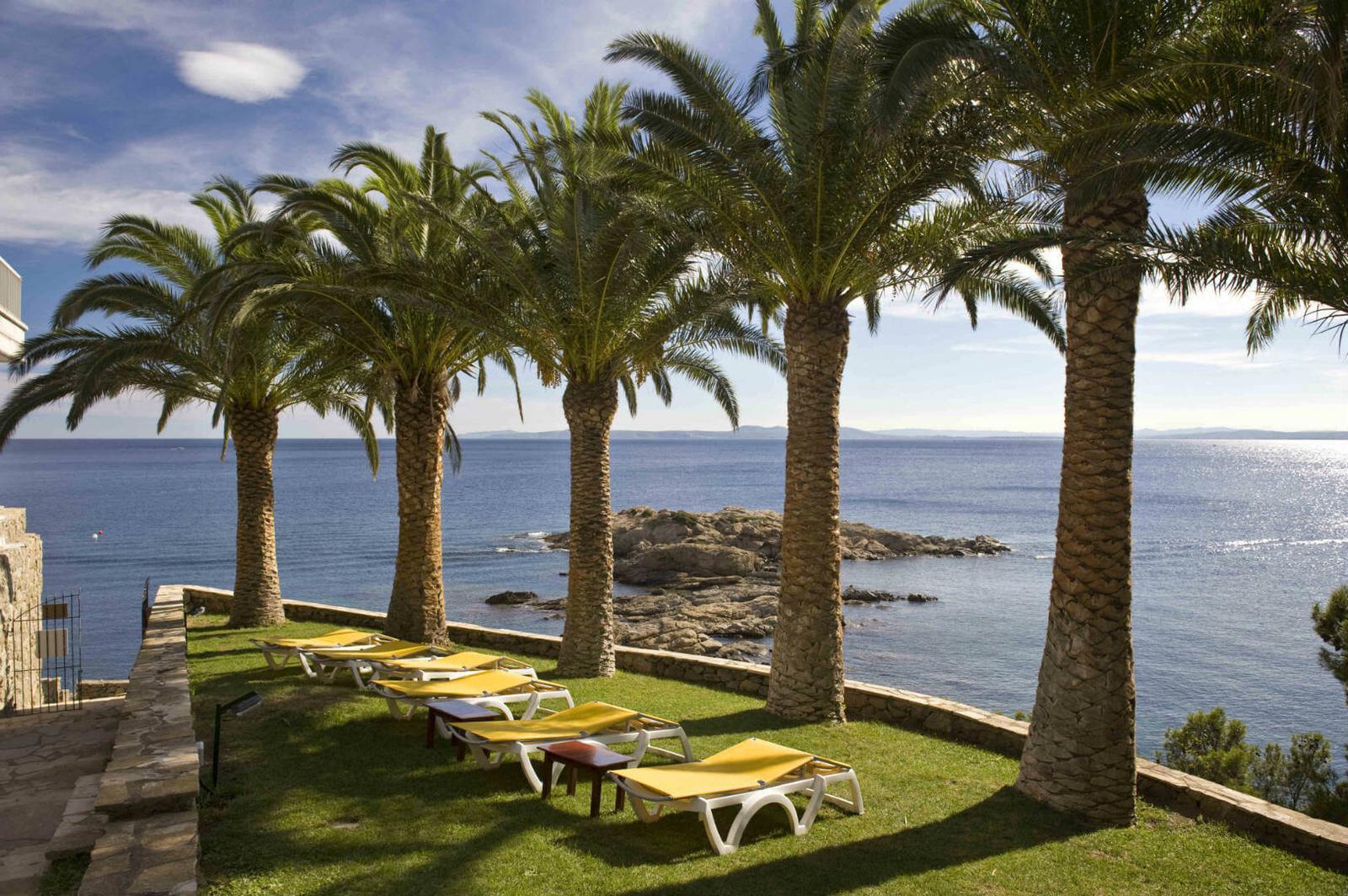 Jardín con palmeras en el hotel Almadraba Park en Roses, Costa Brava