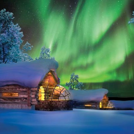 Aurore boréale et chalets enneigés à l'Igloo Village Kakslauttanen la nuit en Finlande