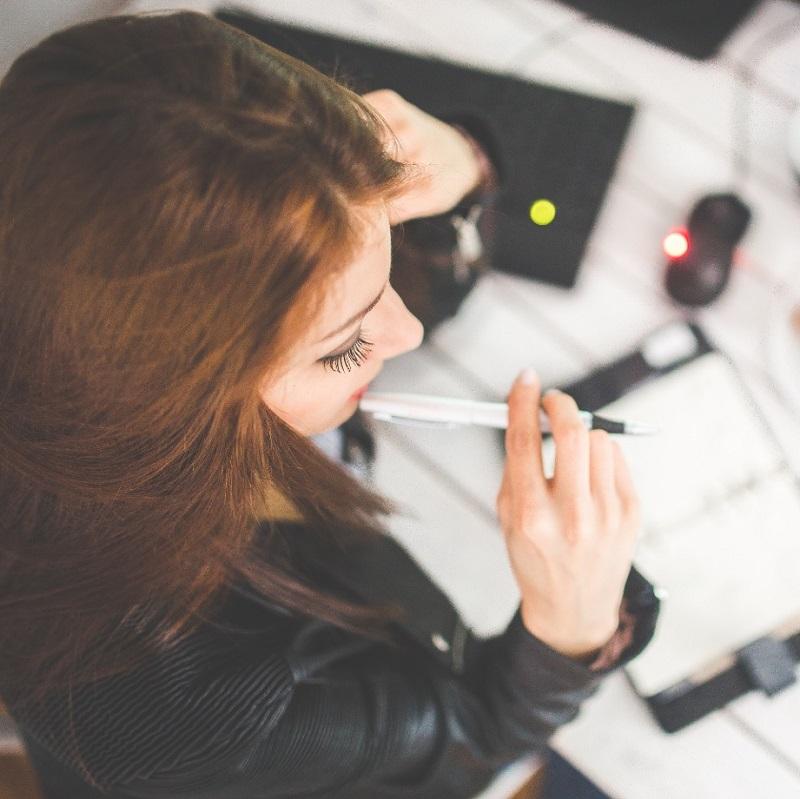 Une jeune femme réfléchit avec son carnet de note et son ordinateur