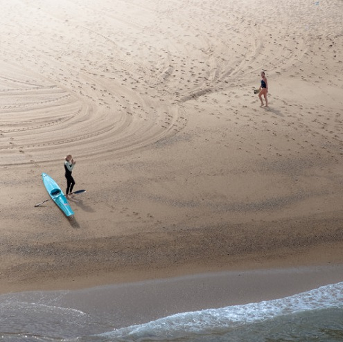 Une kayakiste et une promeneuse sur une plage de Biarritz