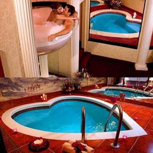 Couple dans un jacuzzi en forme de coupe de champagne et jacuzzi en forme de coeur au Pocono Place Resort aux Etats-Unis