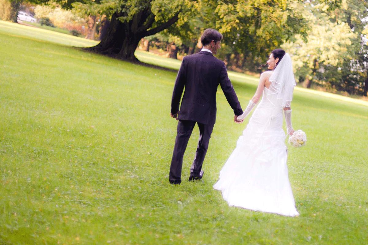 Brautpaar Händchen-haltend auf einer Wiese