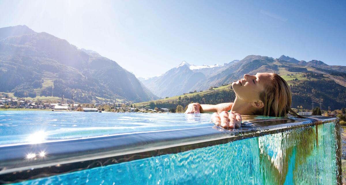 Frau genießt Infinity-Pool im Salzburger Hotel Spa Zell am See.