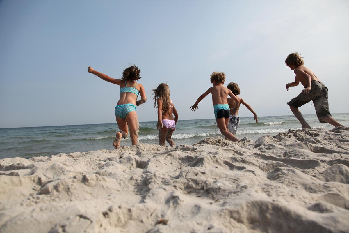 Kinder toben am Strand im Sand.