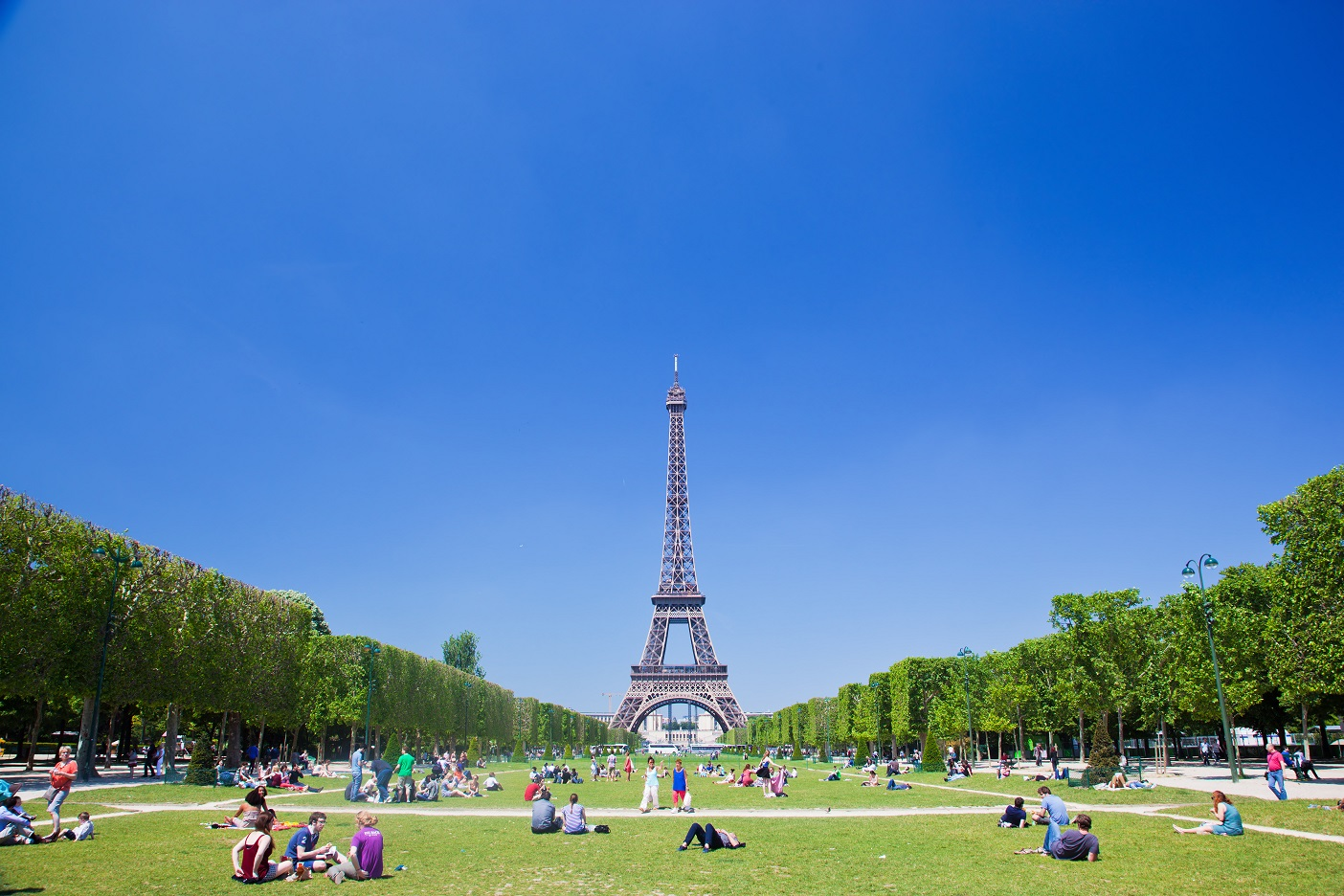 Turistas y locales disfrutando del sol en Champs de Mars.