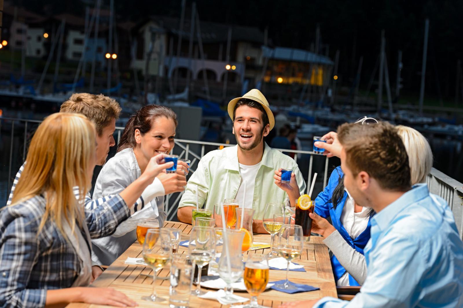 razones por las que nos encanta el verano Young people doing shots at outside bar