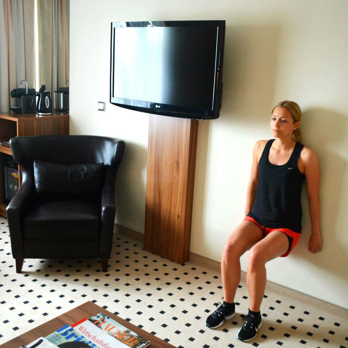 agachamento na parede em quarto de hotel