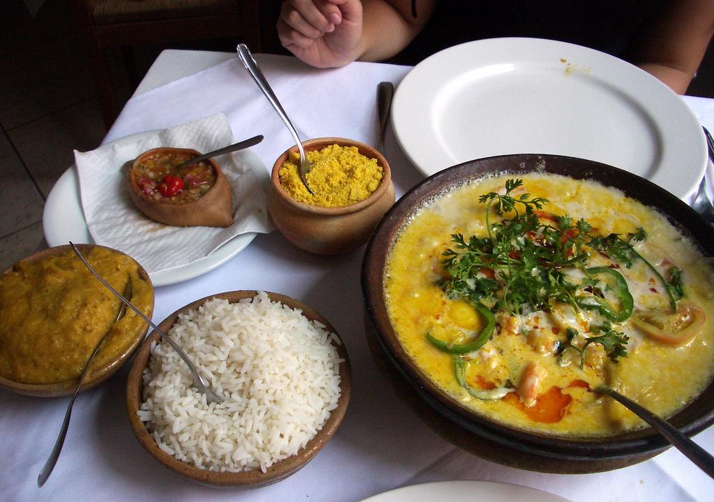 table garnie de moqueca, riz, farofa, vatapa et piment - spécialités culinaires du Brésil