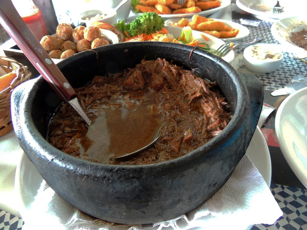 Plat de barreado, ragoût de viande brésilien, coxinha et accompagnements en arrière plan