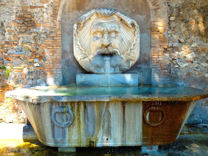 Petite fontaine sortant d'un mur et coulant dans une baignoire en pierre