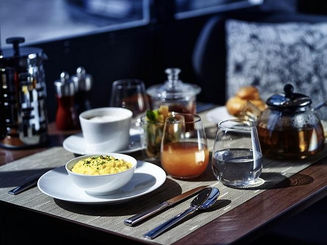 Table dressée de petit-déjeuner au MOLITOR PARIS BY MGALLERY : oeufs brouillés, verre de jus, thé, café, brioche
