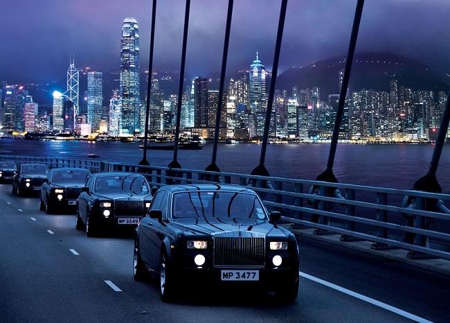 Plusieurs Rolls-Royce mise à disposition par The Peninsula sur le pont de Hong-Kong de nuit