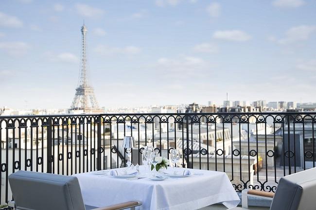 Table dressée sur la terrasse de L'Oiseau Blanc, restaurant de The Peninsula Paris avec vue sur la Tour Eiffel