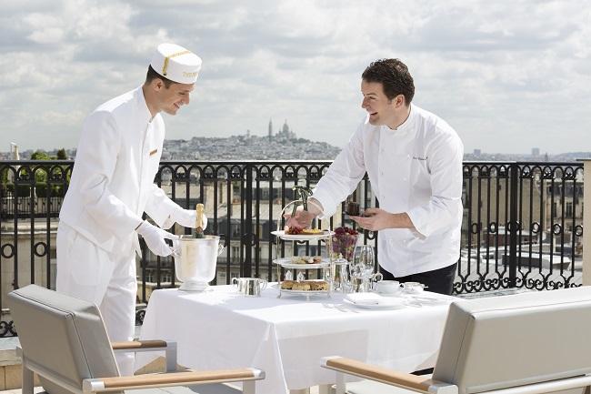 Le chef et le sommelier dressant une table du restaurant L'Oiseau Blanc avec Montmartre en arrière-plan