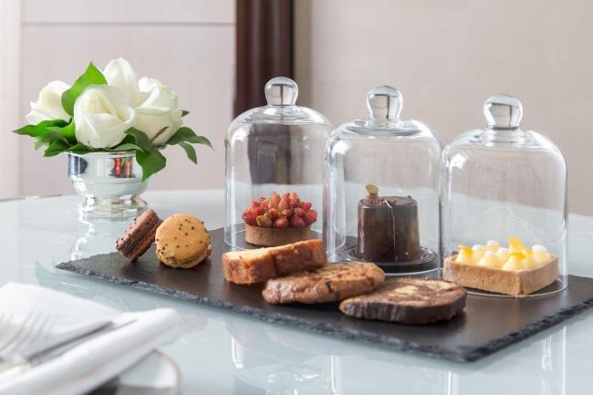 Tranches de gâteau et tartelettes sous cloche servies pour l'afternoon tea de The Peninsula Paris