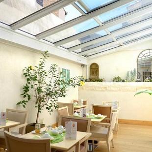 Salle du petit-déjeuner sous la véranda à l'hôtel Aragon