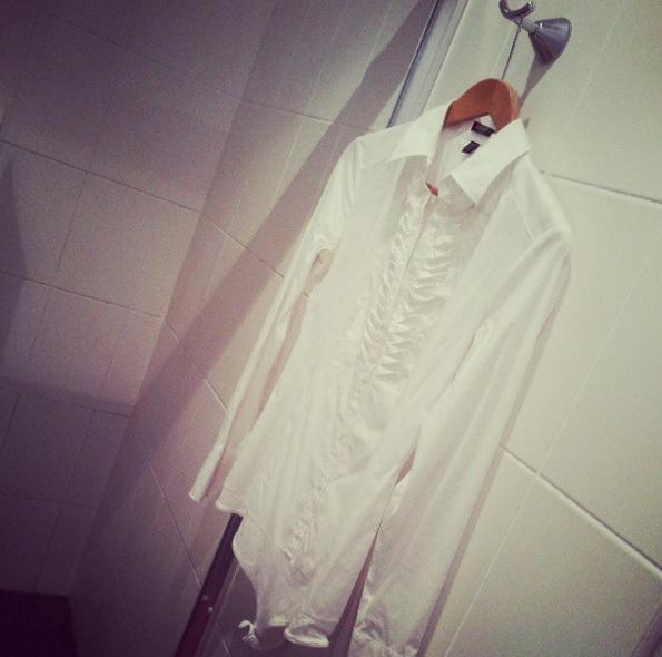 Chemise blanche suspendue dans la salle de bain