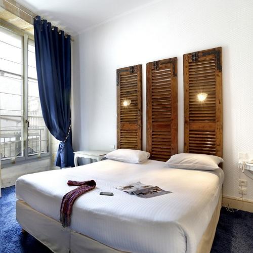Chambre double à l'hôtel La Tour Intendance et tête de lit volets