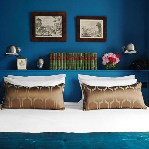 Chambre double à hôtel La Belle Juliette et tête de lit avec livres et images