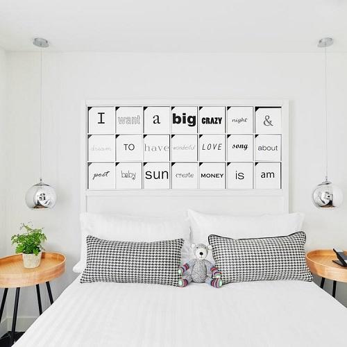 Chambre double à l'hôtel Joke et tête de lit avec des mots