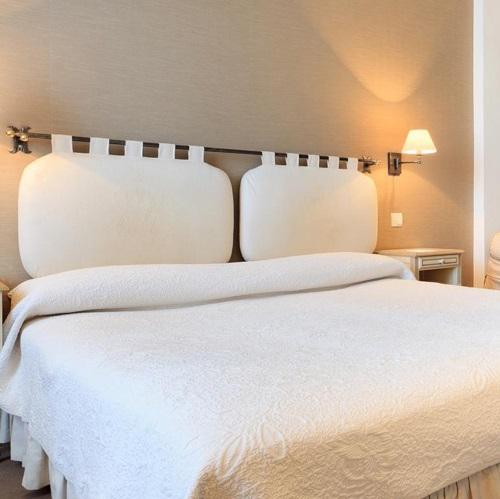 Chambre double à l'hôtel Le Grimaldi et tête de lit avec coussins moelleux
