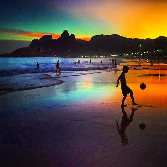 Kleiner Junge der am Strand Fussball spielt. Brasilien