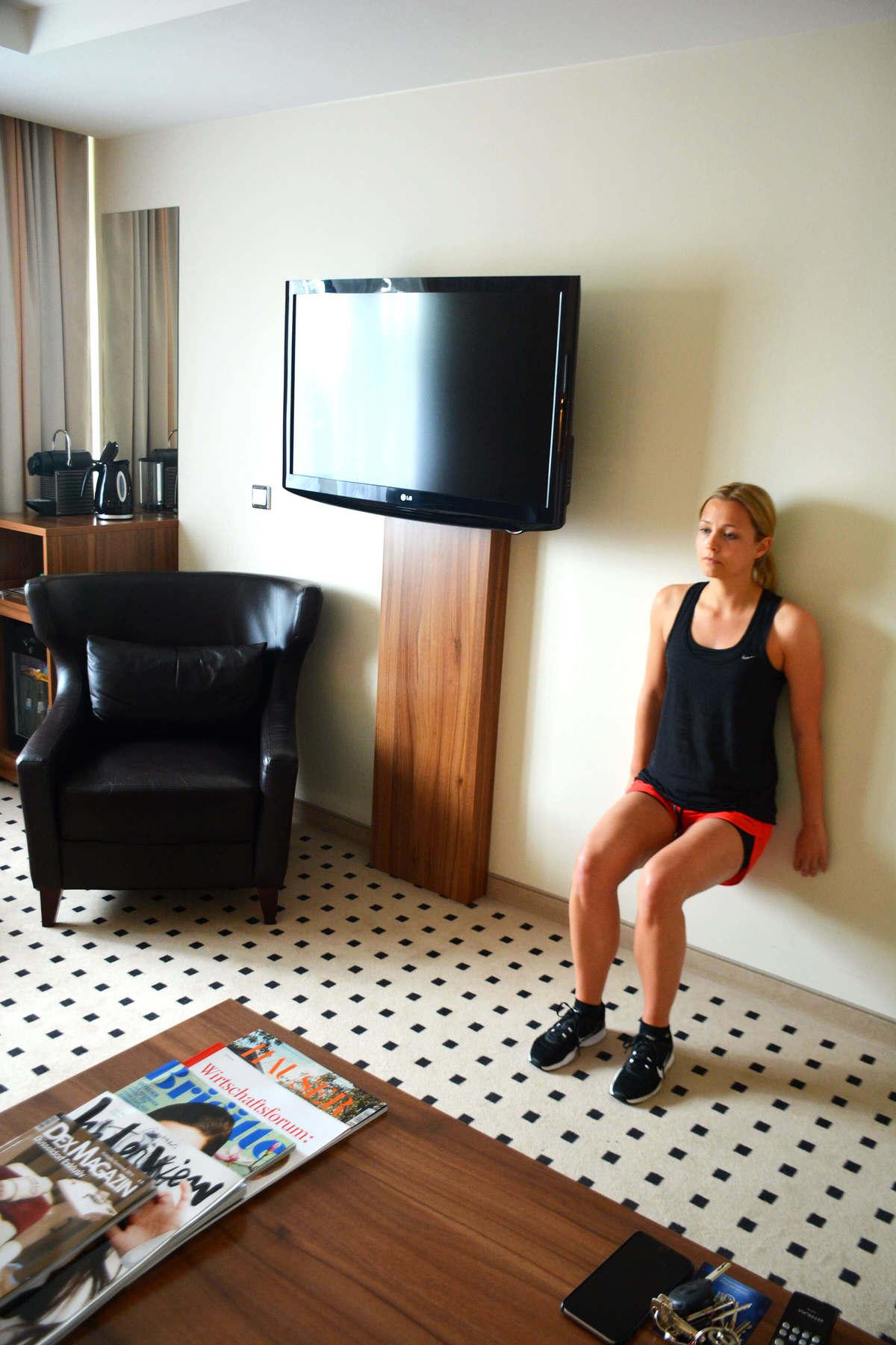 Julia beim Wandsitzen im Hotelzimmer